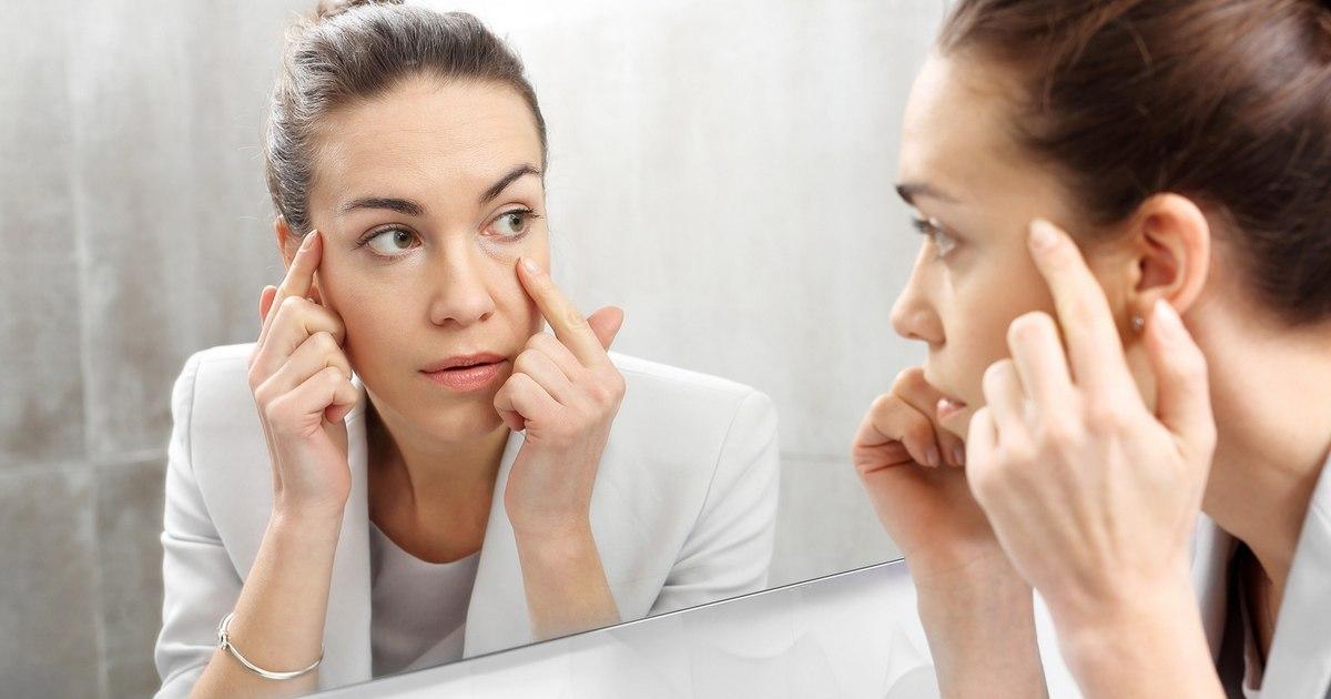 Odbicie w lustrze.Kobieta przegląda się w lustrze dostrzegając pierwsze zmarszczki